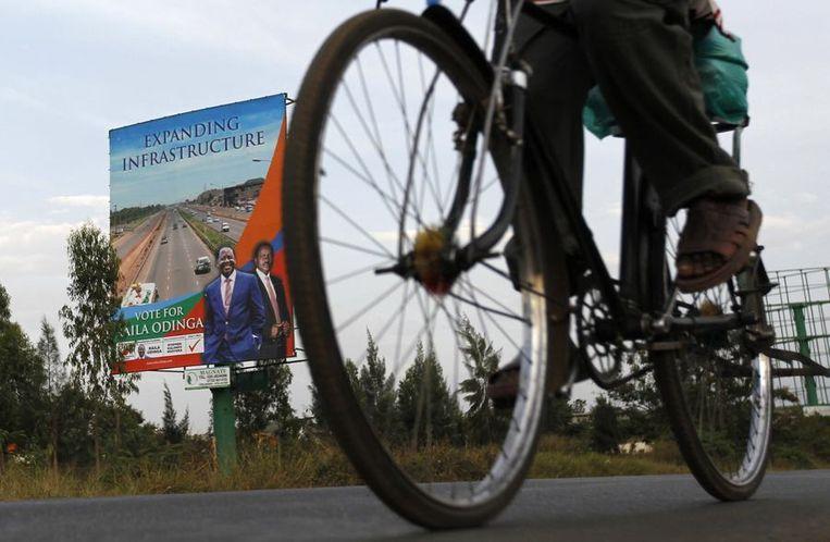 Een man op een fiets passeert een verkiezingsaffiche voor premier Raila Odinga. Beeld reuters