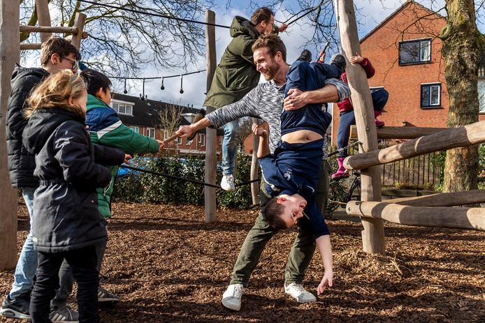 Meester Daan en meester Jaap spelen in de pauze met kinderen op het klimrek.