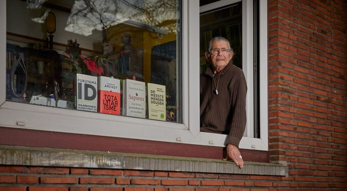 Jan Vermeulen achter zijn raam op de eerste verdieping.  Hij heeft COPD en blijft binnen in verband met de coronacrisis.