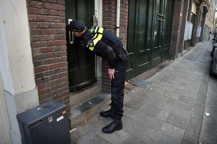 Een wijk agent probeert contact te krijgen met een bewoner in het Oude Westen in Rotterdam. Beeld Marcel van den Bergh / de Volkskrant