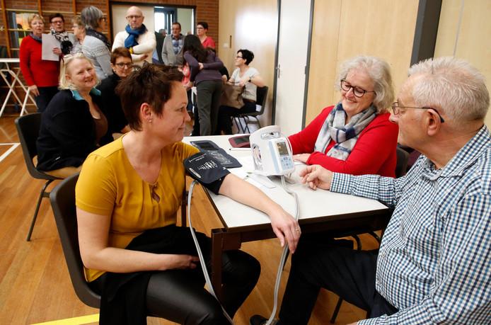 De bloeddruk van Inge Laffeber (links) wordt gemeten door Piet Remery van de EHBO (rechts). Marlies den Doelder (midden) van de dorpsraad houdt toezicht.