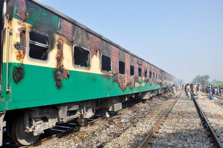 De resten van de uitgebrande trein bij Rahim Yar Khan.  Beeld AFP