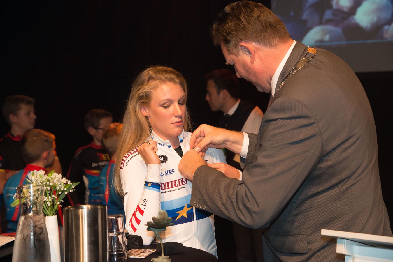 Burgemeester Breunis spelt de zilveren sierspeld op bij Annemarie Worst.