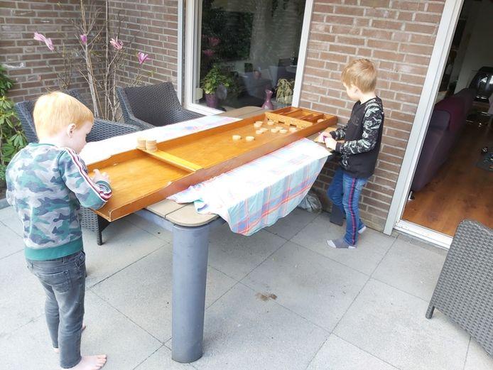 Een ouderwets potje sjoelen! Dat is nog leerzaam ook, want het tellen van de punten is een rekenles op zich. Mick (6) en Robin (8) uit Breda vieren hun staycation met tal van leerzame activiteiten in de achtertuin.