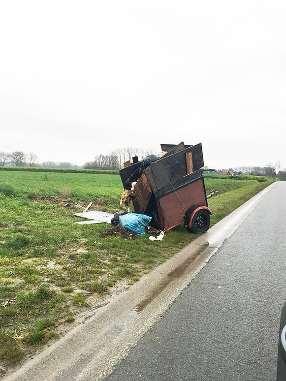 De aanhangwagen in de graskant naast de gewestweg.