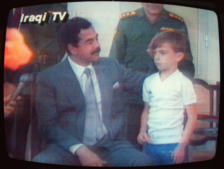 23 augustus 1990:Saddam Hoessein pakt Stuart vast voor het oog van de Irakese tv-camera's.  Beeld Hollandse Hoogte / AFP