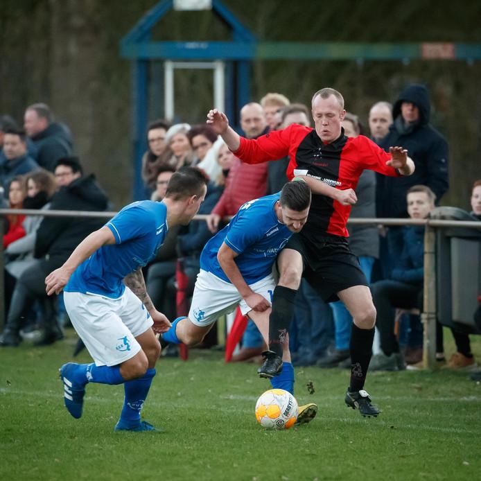 Het publiek in Rucphen ziet hoe Richard Schijven (midden, RSV) en doelpuntenmaker Wesley Heijnen (rechts, Sprundel) een duel om de bal uitvechten.
