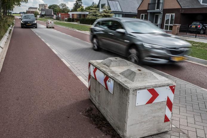 Slalommen tussen de betonblokken door op de Katwijkseweg in Cuijk.