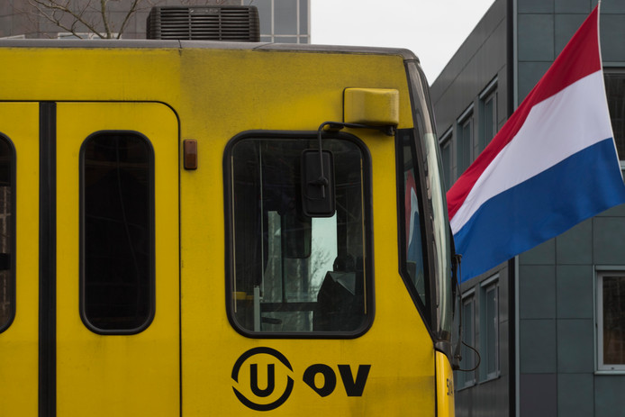 Een tram passeert in Utrecht een vlag die halfstok hangt.