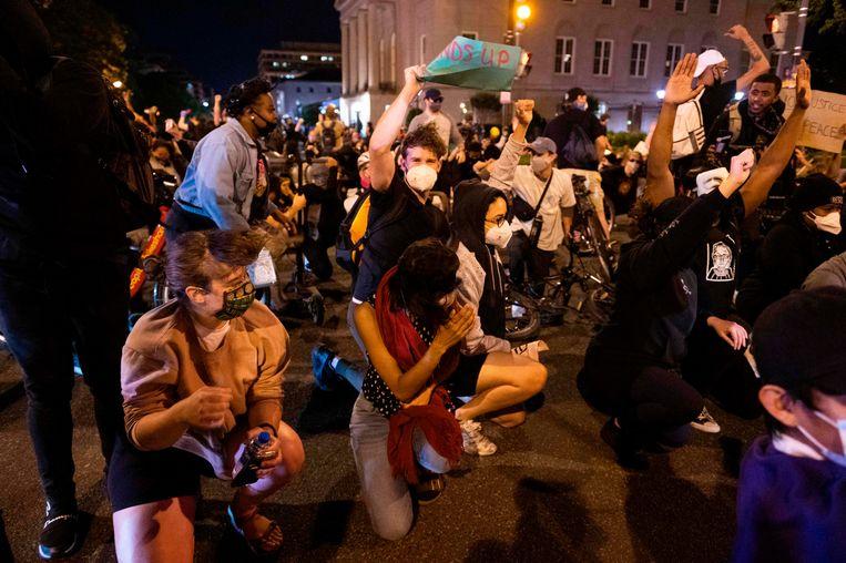 Demonstranten in Washington duiken weg voor de harde wind die een laagvliegende legerhelikopter produceert.  Beeld AFP