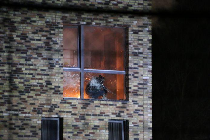 Een man gooit brandende spullen richting de hulpverleners.