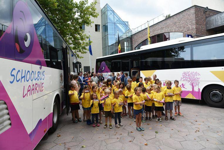 De leerlingen bij hun nieuwe schoolbussen.