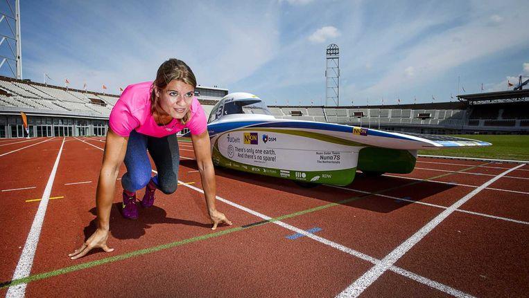 Wereldkampioen sprint Dafne Schippers poseert naast de Nuna 7S van het Nuon Solar Team. De atlete neemt het in Olympisch Stadion op tegen het Nuon Solar Team, de wereldkampioen zonneracen. Beeld anp