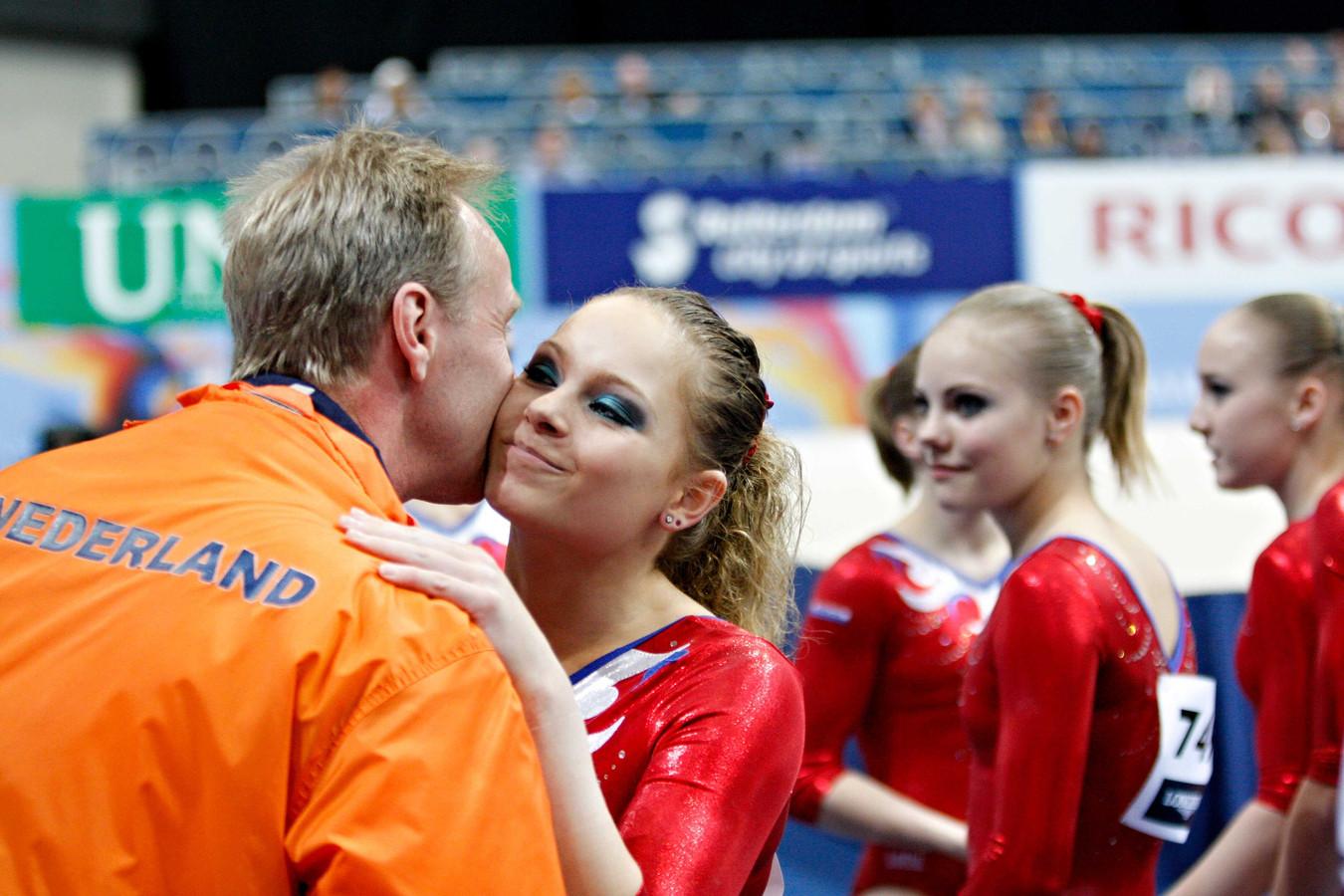 """Joy Goedkoop wordt geknuffeld door coach Vincent Wevers na een geslaagde kwalificatie op het WK turnen 2010. Goedkoop beschuldigde Wevers eerder deze week van mishandeling. ,,Er was op dagelijkse basis sprake van kleineren, schelden, boos worden. Ik ben ook geslagen en geschopt door hem."""""""