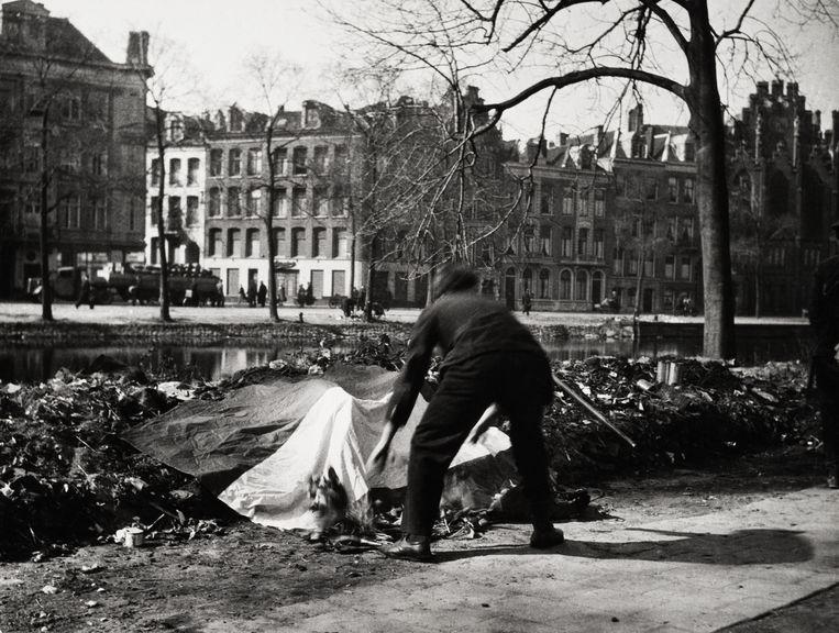 Vlaglegging op het Weteringplantsoen op de plaats waar de Duitsers op 12 maart 1945 tweeëndertig mensen hadden gefusilleerd, Amsterdam 1945. Beeld Cas Oorthuys