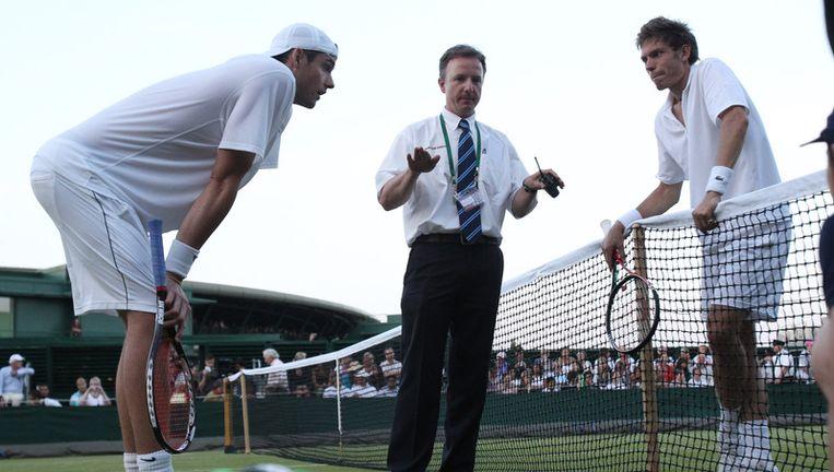 Umpire Soeren Friemel, blij dat hij even staat, stelt Isner (l) en Mahut voor de strijd te staken. Foto AP Beeld