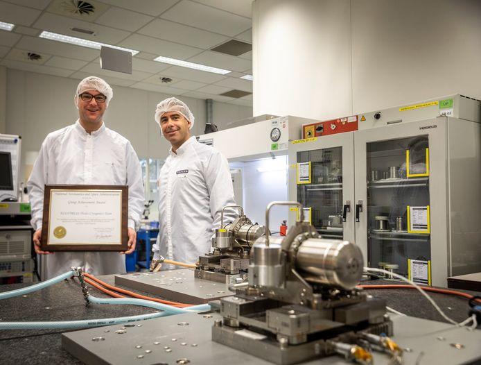 Roel Arts met de ingelijste onderscheiding van Nasa met directeur Hein Druncks van Thales bij enkele van de koelers.