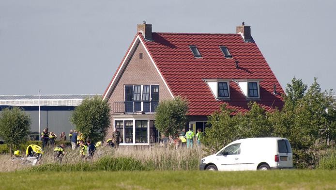 Hulpdiensten doen onderzoek bij de woning in Bitgum waar de Zwitserse straaljager is neergestort