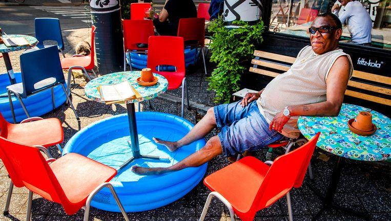 Een man zit met zijn voeten in een zwembadje op een terras aan de Nassaukade. Beeld anp