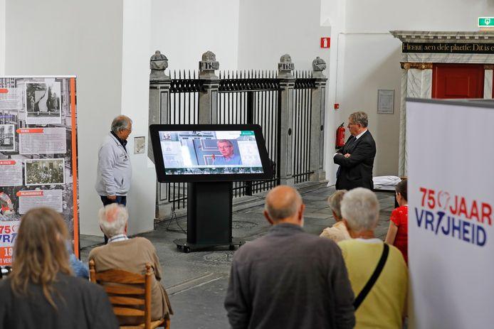Frans Nix van Filmclub Phoenix (links) en burgemeester Gregor Rensen bij het beeldscherm van de tentoonstelling '75 Jaar vrijheid in Brielle' in de Sint-Catharijnekerk.