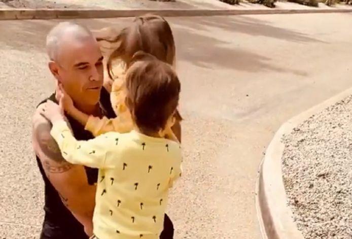 Zanger Robbie Williams sluit zijn zoon en dochter in zijn armen.