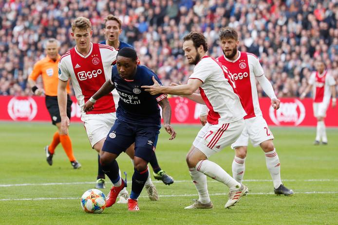 Tijdens Ajax-PSV probeert de Ajax-defensie Steven Bergwijn af te houden.