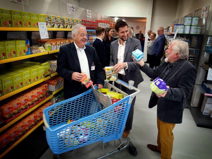 Oud-voorzitter Arie van Hoven (rechts) en voorzitter Arie de Bruin leggen wethouder Eelke Kraaijeveld bij de opening van de nieuwe locatie november vorig jaar uit hoe cliënten zelf kunnen winkelen. Dat kan momenteel niet.