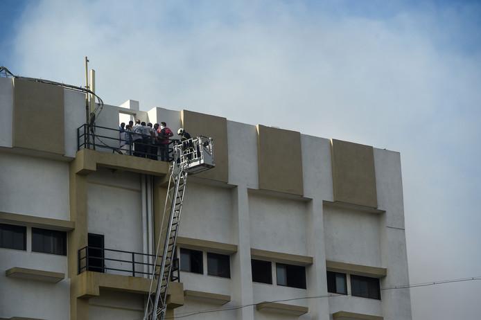 Brandweermannen proberen werknemers van de telefoonmaatschappij met hoogwerkers uit het kantoorgebouw te redden.