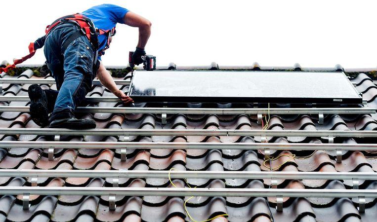 Een monteur plaats zonnepanelen op het dak van een woonhuis. Beeld ANP