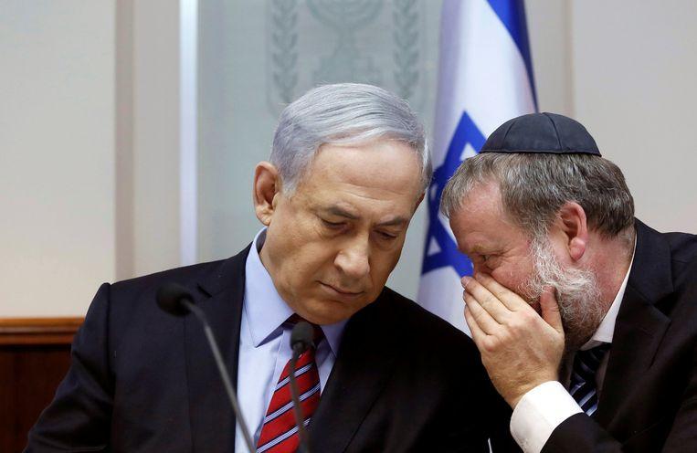 Openbaar aanklager Avichai Mandelblit is een voormalige kabinetssecretaris van Netanyahu. Hier overlegt hij  in 2014 met de premier tijdens de wekelijkse kabinetsvergadering.  Beeld Reuters