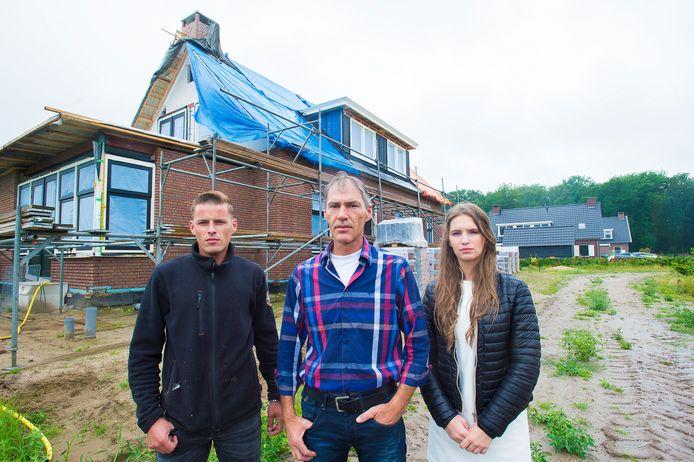 Drie jaar geleden aan de Oudedijk in Uddel: Gerrit van den Brink wordt geflankeerd door zijn dochter en schoonzoon voor hun bijna voltooide dubbele woning waar de gemeente een bouwstop op legde. Sindsdien staat het blok er nog net zo bij.