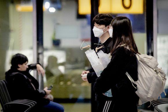 Reizigers op Schiphol dragen een mondmasker. Viroloog Marc Van Ranst (KU Leuven) benadrukt dat enkel zieke mensen of hulpverleners die met zieke mensen werken, die horen te dragen.