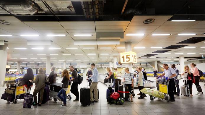 Reizigers die zijn aangekomen op Schiphol staan in de rij voor voor controle van de douane.