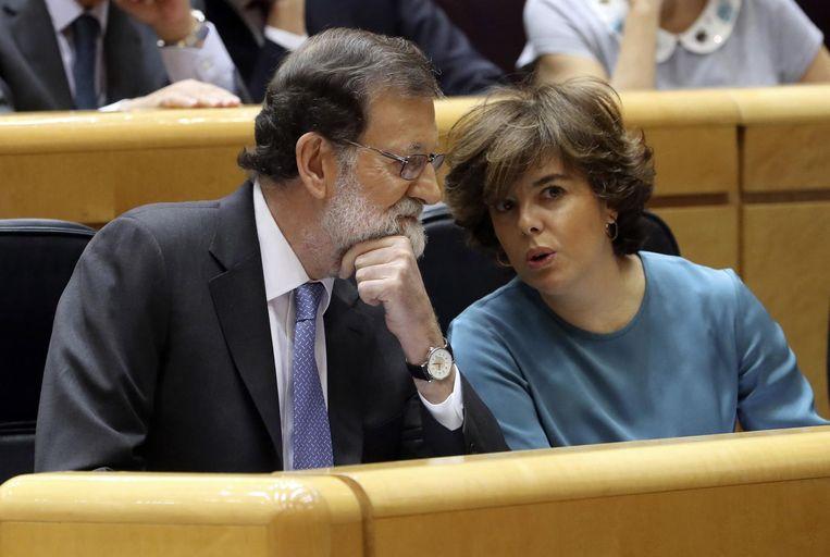 De Spaanse premier Mariano Rajoy praat met Soraya Saez de Santamaria. Beeld epa
