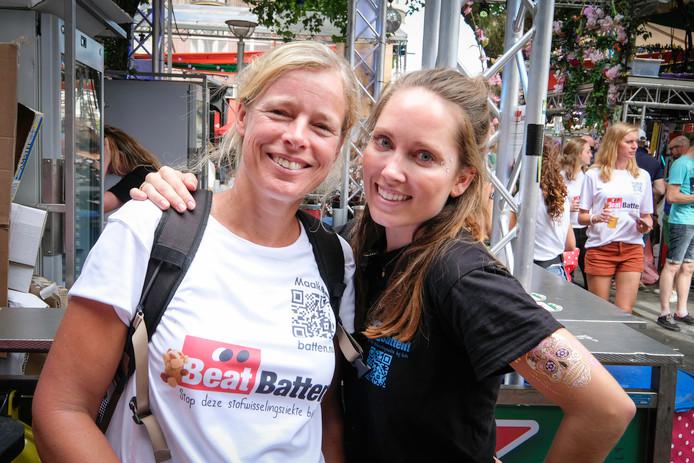 Maaike den Hollander (links) met een barmedewerker van het Faberplein. Bij beiden prijkt de QR-code op het shirt, die mensen de mogelijkheid geeft om met de mobiele telefoon geld te doneren.