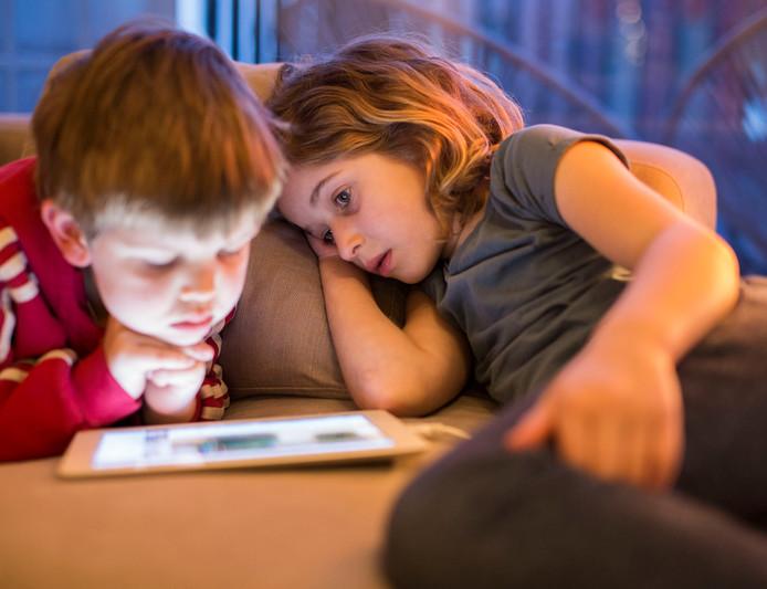 Thuis bankhangen en iPad kijken. Broer en zus van vier en acht jaar kijken samen naar een film op de ipad . Foto and copyright Amaury Miller