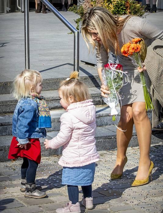 Koningin Máxima praat met kleine kinderen.