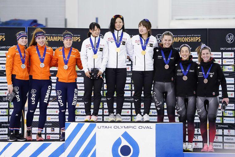 Melissa Wijfje, Antoinette de Jong en Ireen Wüst op de tweede trede van het podium van de ploegenachtervolging, naast de Japanse en Canadese vrouwen. Beeld ANP