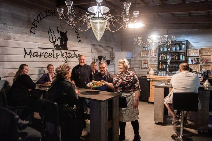 Breda - Nancy (rechts met schotel) en Marcel Villerius (zwarte koksbuis midden) van de Tafel van 8 serveren een gerecht uit op hun nieuwe terras.