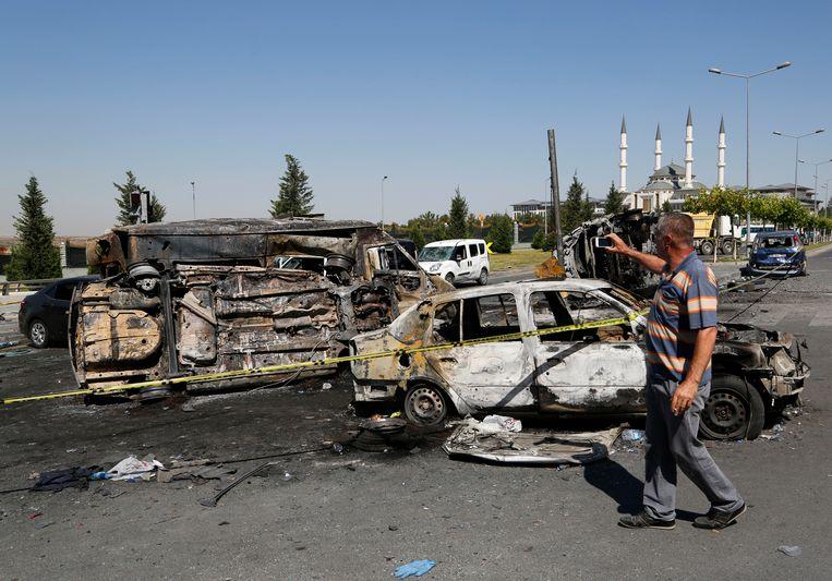 Een man neemt zondag foto's van door een luchtaanval verwoeste voertuigen van burgers en militairen nabij het presidentiële paleis in Ankara. Beeld ap
