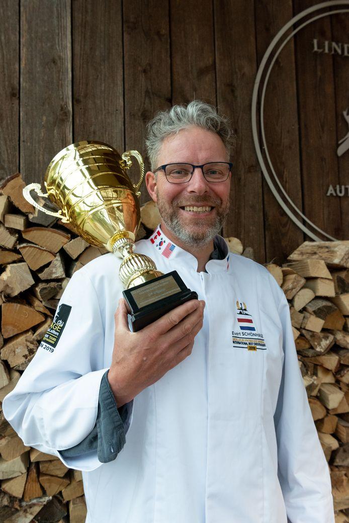 Evert Schönhage trots met zijn beker. Daarop staat: 'World Contest of the Best Cheesemonger 2019 / 1st place / International Best Cheesemonger / Tours France'.