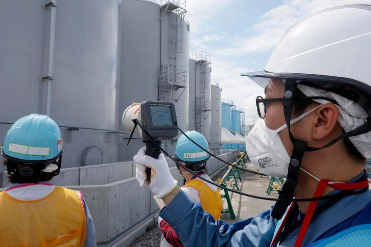Een medewerker van Tepco meet in Fukushima het stralingsniveau rond opslagcontainers die radioactief water bevatten.