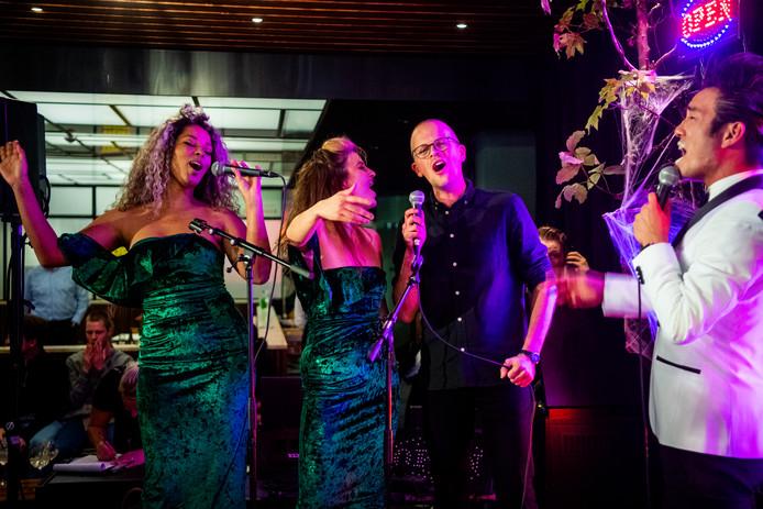 Verslaggever Lex Bezemer in duet met Wei Not Sing (rechts) en zijn danseressen.