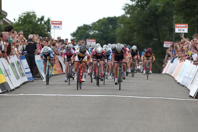 Lorena Wiebes (oranje fiets) wint de sprint van het peloton en eindigt als derde).