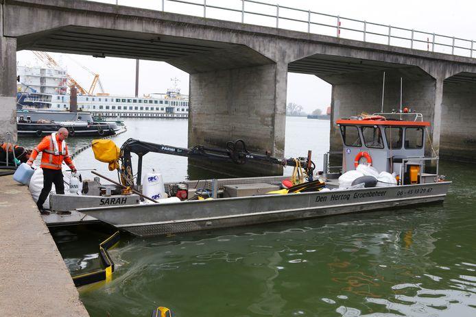 Spullen aan boord en gaan. Een van de specialisten die de olie in de haven opruimen, stapt op het werkschip in de haven van Hardinxveld.
