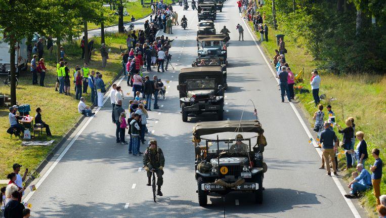 Oude (geallieerden) legervoertuigen trekken in 2014 door de straten van Eindhoven, zeventig jaar na Operatie Market Garden. Beeld anp