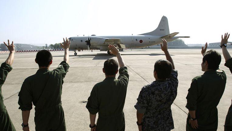 Een Japans vliegtuig dat ook vanuit Australië gaat deelnemen aan de zoektocht naar de verdwenen boeing wordt uitgezwaaid. Beeld ap