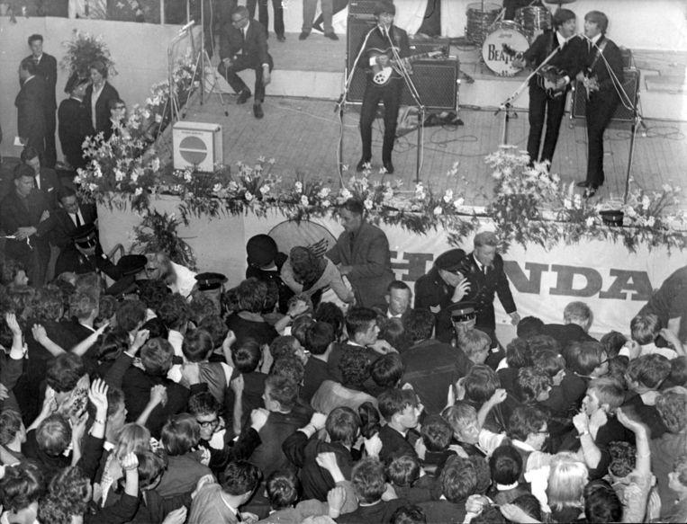 The Beatles geven een concert in Blokker op 7 juni 1964. . V.l.n.r. George Harrison, invaldrummer Jimmy Nolan (net zichtbaar), Paul McCartney en John Lennon.Politieagenten houden het publiek in bedwang. Beeld anp