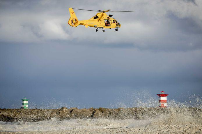 Een helikopter van de kustwacht tijdens de hervatte zoektocht naar de vermiste watersporters bij het Noordelijk Havenhoofd. De kustwacht, politie, brandweer en KNRM zijn op zoek naar mogelijk nog drie vermisten.