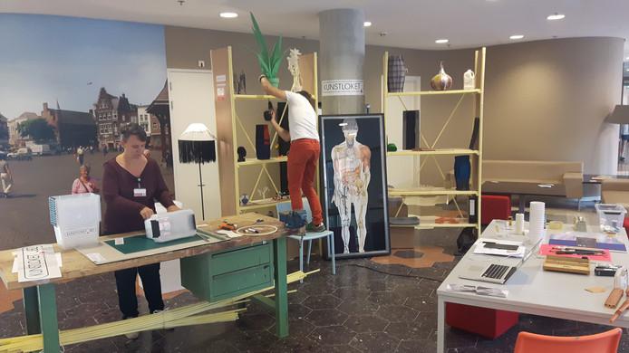 Nicole Driessens en Ivo van den Baar zijn het 'Kunstloket' op de Boulevard van het JBZ aan het inrichten.